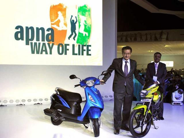 Managing Director of Suzuki motorcycle Kondo (C) poses with new vehicles during the 2012 Auto Expo in New Delhi. AFP Photo/ Sajjad Hussain
