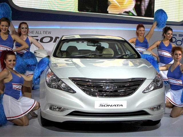 Cheer leaders from London pose with the new Sonata car at Hyundai pavilion at Auto Expo 2012 at Pragati Maidan. PTI Photo / Vijay Verma