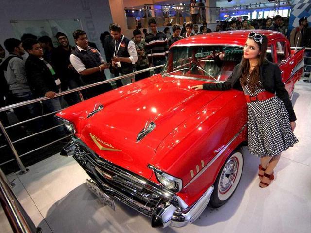 A model poses with a vintage car at Chevrolet pavilion at Auto Expo 2012 at Pragati Maidan in New Delhi. PTI Photo / Vijay Verma