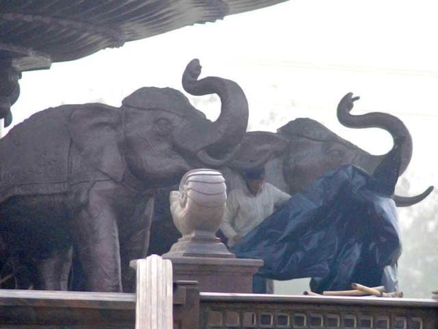Indian-laborers-work-near-covered-elephant-statues-at-Ambedkar-Park-in-Noida-on-the-outskirts-of-New-Delhi-AP-Photo-Saurabh-Das