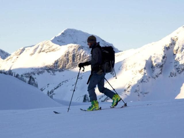 Silhouetted-against-the-snow-capped-mountains-skier-Danny-Uhlmann-is-seen-backcountry-skiing-near-McGillivray-Pass-Lodge-located-in-the-southern-Chilcotin-Mountains-of-British-Columbia-AP-Photo