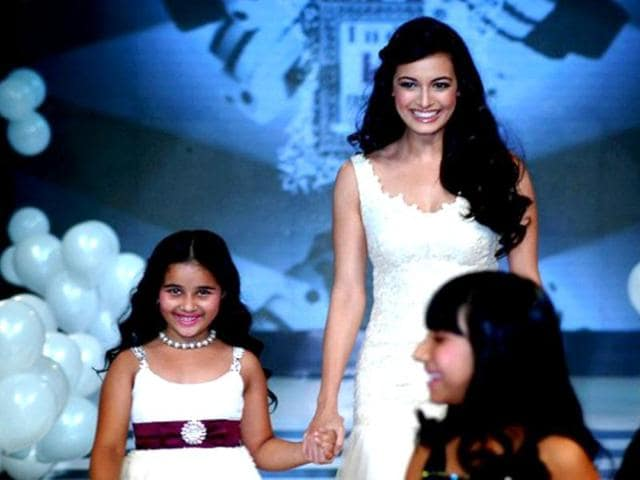 Dia-holds-a-little-girl-s-hand-as-she-walks-the-ramp-for-Rocky-S