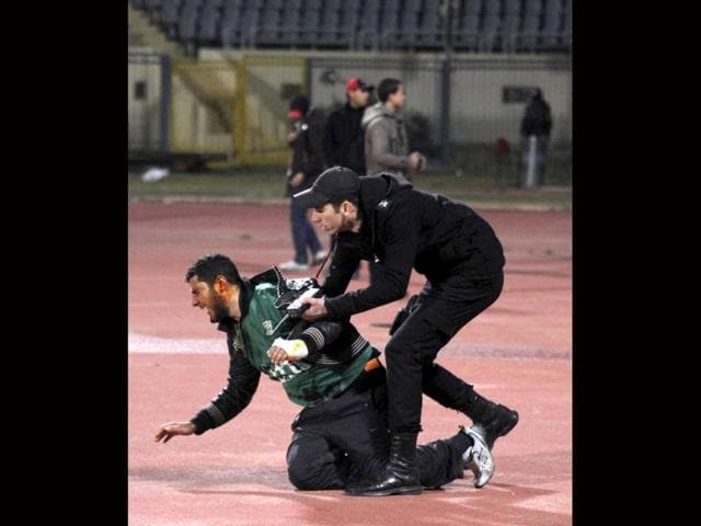 A-policeman-arrests-an-injured-rioting-soccer-fan-as-chaos-erupts-at-a-soccer-stadium-in-Port-Said-city-in-Egypt-Seventy-three-people-were-killed-and-at-least-1-000-injured-on-Wednesday-after-a-soccer-pitch-invasion-in-the-Egyptian-city-of-Port-Said-a-health-ministry-official-said-in-an-incident-that-one-player-described-as-a-war-not-football-Reuters