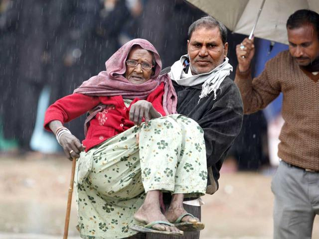 A-person-carries-an-elderly-woman-after-she-cast-her-vote-in-Gonda-district-in-the-Indian-state-of-Uttar-Pradesh-AP-Photo-Rajesh-Kumar-Singh