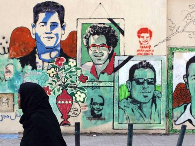 An-Egyptian-woman-passes-a-mural-depicting-unidentified-slain-soccer-fans-killed-following-a-soccer-match-last-week-and-Arabic-that-reads-we-bring-them-their-rights-or-we-die-like-them-in-Cairo-Egypt-AP-Nasser-Nasser