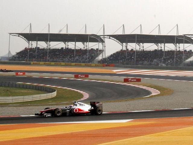 Formula-One-motor-racing-drivers-Narayan-Karthikeyan-L-and-Karun-Chandhok-R-of-India-and-managing-director-and-CEO-of-Jaypee-Sports-International-Sameer-Gaur-C-present-a-giant-sized-Indian-Formula-One-ticket-during-the-launch-of-tickets-for-the-2011-Formula-One-in-Greater-Noida