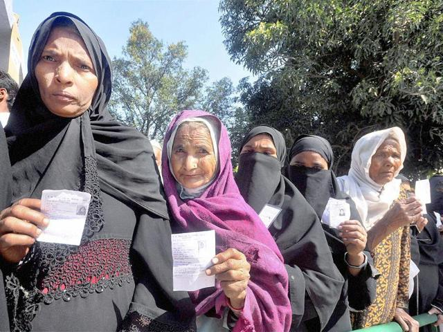 Voters-display-their-identity-cards-as-they-wait-to-cast-their-votes-at-a-polling-station-during-the-4th-phase-of-Uttar-Pradesh-assembly-elections-in-Pratapgarh-PTI-Photo