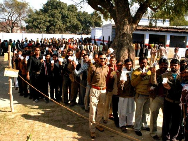 Voters-display-their-identity-cards-as-they-wait-to-cast-votes-at-a-polling-station-during-4th-phase-of-Uttar-Pradesh-assembly-elections-in-Hardoi-PTI-Photo
