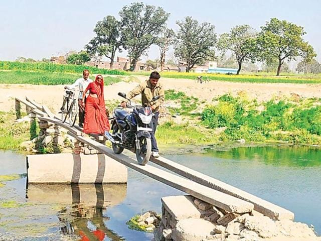 Two-cement-poles-serve-as-a-bridge-across-river-Nakatiya-for-Pahadpur-villagers-HT-Sachin-Saini