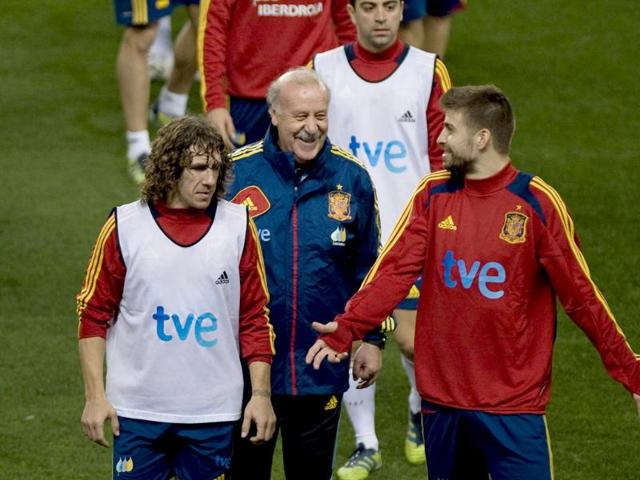 Spain-s-coach-Vicente-del-Bosque-C-talks-with-Spain-s-defender-Carles-Puyol-and-defender-Gerard-Pique-R-during-a-training-sesion-at-the-Rosaleda-Stadium-in-Malaga--on-the-eve-of-a-friendly-football-match-against-Venezuela-AFP-PHOTO-JORGE-GUERRERO