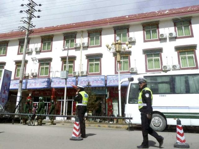 In-this-photo-Chinese-paramilitary-policemen-left-stand-guard-while-traffic-police-officers-control-traffic-near-barricades-set-up-along-the-main-street-of-Aba-county-seat-in-China-s-Sichuan-province-China-s-stifling-lockdown-of-this-Tibetan-monastery-town-has-not-only-been-about-patrolling-its-otherwise-sleepy-streets-Beijing-is-also-policing-the-minds-of-a-community-at-the-center-of-self-immolation-protests-against-Chinese-rule-AP-Photo-Gillian-Wong