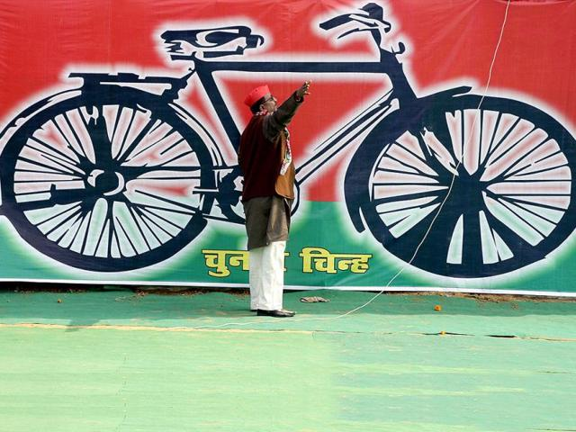 A-SP-worker-gestures-in-front-of-a-banner-with-the-party-s-electoral-symbol-in-Allahabad