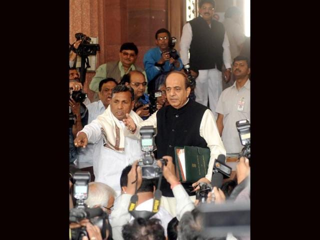 Dinesh-Trivedi-C-gestures-as-he-arrives-at-Parliament-flanked-by-minister-of-state-for-railway-Muniyappa-L-as-they-are-surrounded-by-media-representatives-in-New-Delhi-Indian-Railways-Minister-Dinesh-Trivedi-presents-the-railway-budget-for-the-fiscal-year-to-March-2012-13-in-Parliament-AFP-Photo-Raveendran