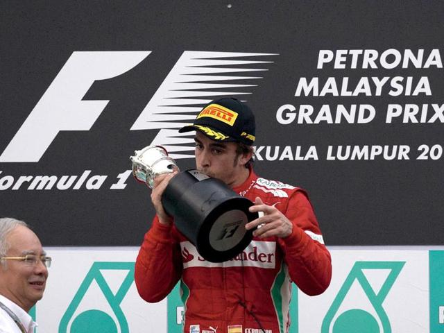 Ferrari-driver-Fernando-Alonso-C-of-Spain-kisses-his-winning-trophy-after-receiving-it-from-Malaysian-prime-minister-Najib-Razak-2nd-L-during-the-ceremony-of-Formula-One-s-Malaysia-Grand-Prix-at-the-Sepang-International-Circuit-AFP-Photo-Saeed-Khan