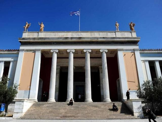 Visitors-sit-outside-the-National-Archeological-museum-in-Athens-Faced-with-massive-public-debt-as-it-moves-into-a-fifth-year-of-recession-Greece-is-finding-that-its-fabled-antiquity-heritage-is-proving-a-growing-burden-AFP-Photo-Aris-Messinis