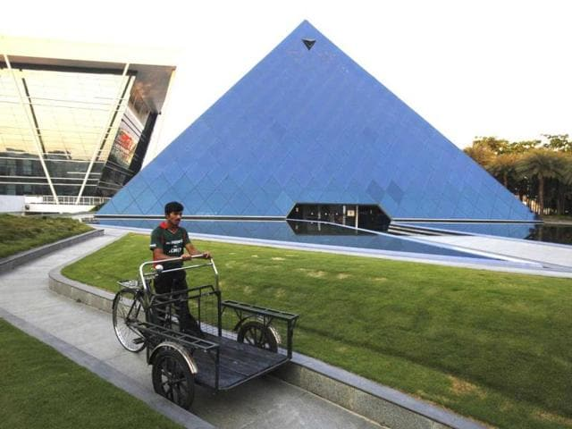 A-man-pushing-a-tricycle-cart-walks-in-front-of-a-pyramid-shaped-building-made-out-of-glass-in-the-Infosys-campus-at-Electronics-City-in-Bangalore-India-s-IT-industry-with-Bangalore-firms-forming-the-largest-component-is-now-worth-an-annual-100-billion-and-growing-14-percent-per-year-Reuters