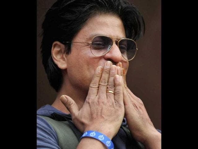 Shah Rukh Khan blows a flying kiss to his fans in the stadium.