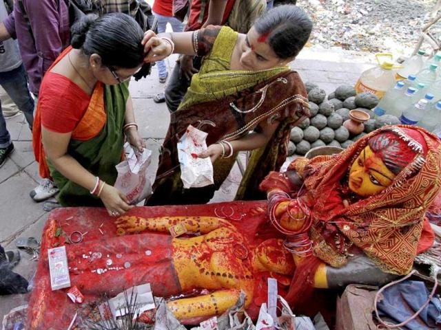 A married woman puts vermilion powder on the forehead of another married in front of an idol of Hindu mythological characters Savitri and her husband Satyaban on Bengali New Year in Kolkata. AP/Bikas Das