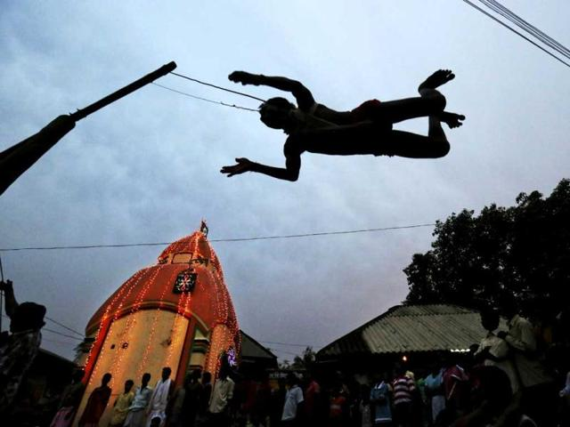 A Hindu devotee swings on a rope next to a Lord Shiva Temple during the Charak ritual in the Hoogly district, near Kolkata. AP/Kevin Frayer