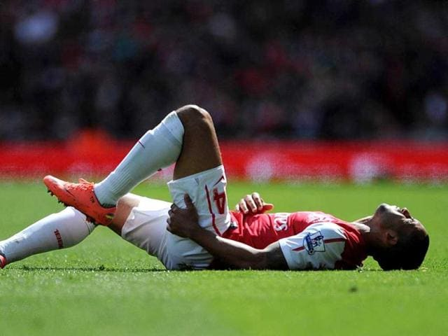 Arsenal-s-Theo-Walcott-lies-injured-on-the-pitch-during-the-English-Premier-League-soccer-match-against-Chelsea-at-the-Emirates-Stadium-London-The-match-ended-in-a-0-0-draw-AP-Photo-Anthony-Devlin