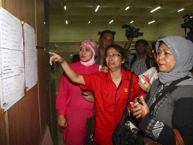 A-relative-weeps-as-she-inspects-the-list-of-passengers-reportedly-on-board-a-missing-Russian-airplane-at-Halim-Perdanakusuma-Airport-in-Jakarta-Indonesia-AP-Photo-Tatan-Syuflana