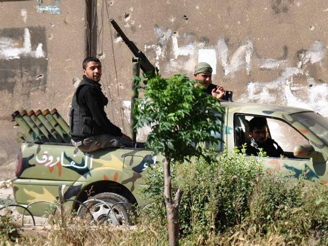 Syrian-rebels-sit-on-their-armored-vehicle-as-they-patrol-at-Khaldiyeh-neighborhood-in-Homs-province-central-Syria-AP-Fadi-Zaidan