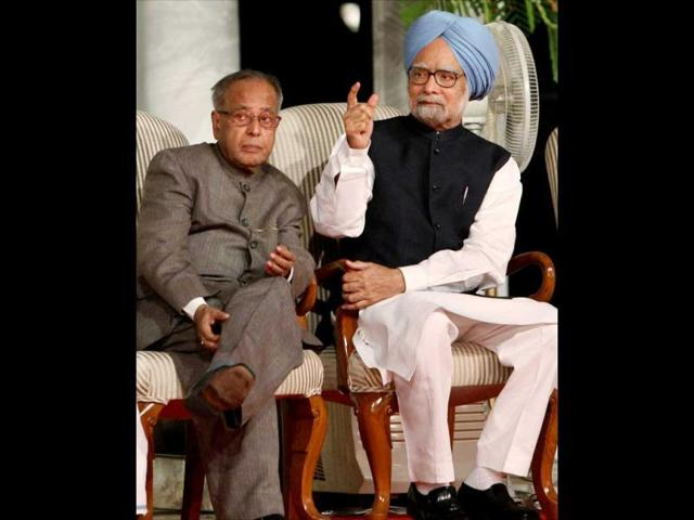 Prime-Minister-Manmohan-Singh-talks-with-Finance-Pranab-Mukherjee-during-the-release-of-a-report-of-United-Progressive-Alliance-titled-Report-to-the-People-2011-2012-on-its-third-anniversary-in-New-Delhi-on-Tuesday--PTI-Photo