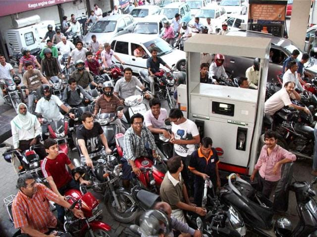 People line up to fill their vehicles at an oil pump after the announcement of hike in petrol prices, in Gurgaon. PTI photo