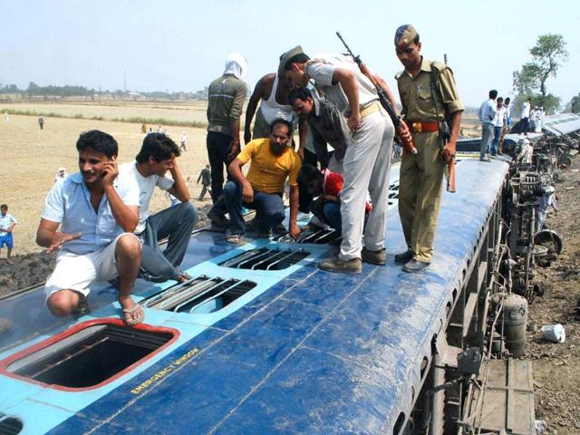 Rescue-personnel-and-bystanders-gather-on-the-wreckage-of-The-Doon-Express-at-Jaunpur-some-210kms-east-of-Lucknow-as-they-search-for-survivors--AFP-PHOTO-STR