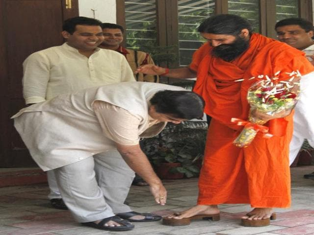 BJP-President-Nitin-Gadkari-touches-Baba-Ramdev-s-feet-during-their-meeting-at-Gadkari-s-residence-in-New-Delhi-HT-Photo-Arvind-Yadav