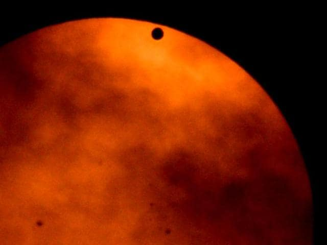 Venus-begins-to-cross-the-sun-s-face-during-the-transit-of-Venus-as-seen-from-the-west-side-of-Manhattan-in-New-York-AFP-Photo-Stan-Honda