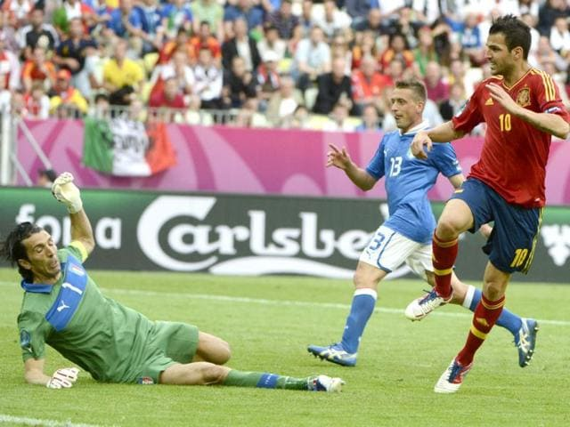 Spanish-midfielder-Cesc-Fabregas-scores-against-Italian-goalkeeper-Gianluigi-Buffon-during-the-Euro-2012-championships-football-match-Spain-vs-Italy-at-the-Gdansk-Arena-AFP-Pierre-Philippe-Marcou