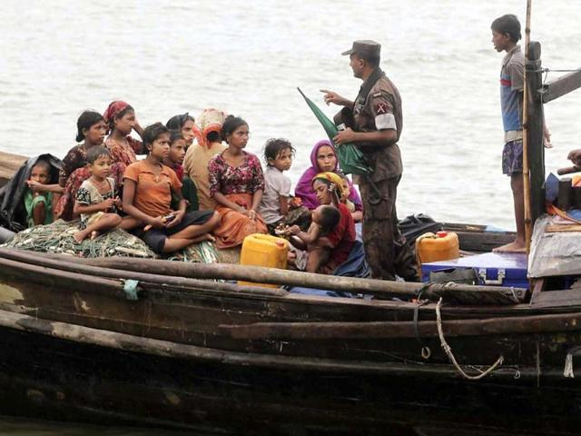 A-Bangladeshi-Border-Police-officer-speaks-with-Rohingya-Muslims-who-fled-Myanmar-to-Bangladesh-to-escape-religious-violence-after-they-were--intercepted-crossing-the-Naf-River-by-the-border-authorities-in-Taknaf-Bangladesh-AP-Photo-Anurup-Titu