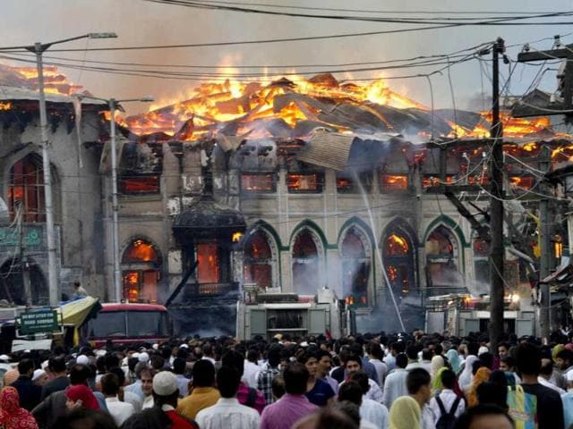 Kashmiri-residents-watch-as-firefighters-try-to-extinguish-a-fire-at-the-nearly-200-years-old-Sheikh-Abdul-Qadir-Jeelani-shrine-popularly-known-as-Ghaus-e-Azam-or-Dastgeer-Sahab-in-downtown-Srinagar-AP-Dar-Yasin