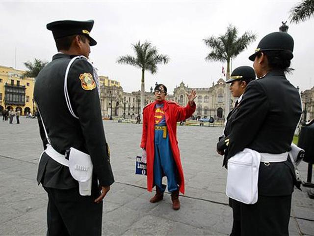 Avelino-Chavez-wearing-his-signature-Superman-costume-talks-with-tourist-police-in-the-main-square-in-downtown-Lima-Peru-Friday-June-15-2012