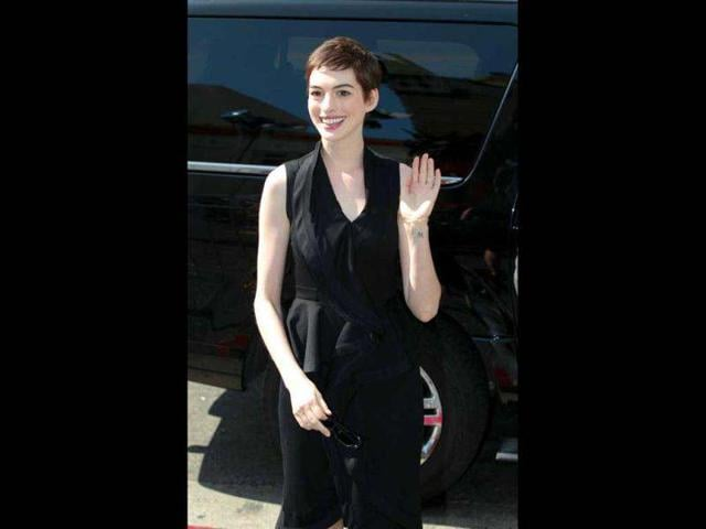 Actress-Anne-Hathaway-waves-as-she-arrives-for-a-hand-and-footprint-ceremony-for-director-Christopher-Nolan-in-the-forecourt-of-the-Grauman-s-Chinese-Theatre-in-Hollywood-California