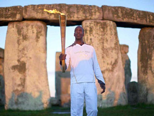 Former-US-Olympic-athlete-Michael-Johnson-poses-for-pictures-with-the-2012-London-Olympic-Flame-at-the-world-heritage-site-of-Stonehenge-in-south-west-England-AFP-Photo