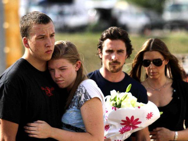 A couple embraces each other as actor Christian Bale holds flowers before placing them at the memorial across the street from the Century 16 movie theater in Aurora, Colorado. The memorial was created for the victims of the mass shooting that occured at the theater last Friday.