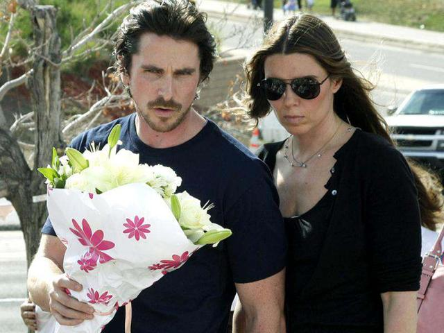 Actor Christian Bale and his wife Sandra Blazic look at the flowers and cards at the memorial across the street from the Century 16 movie theater.