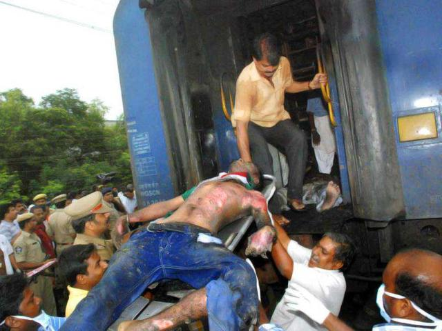 Indian Railway officials take out a body of a passenger from a burnt coach of a passenger train, at Nellor nearly 500 kilometers (310 miles) south of Hyderabad. AP Photo