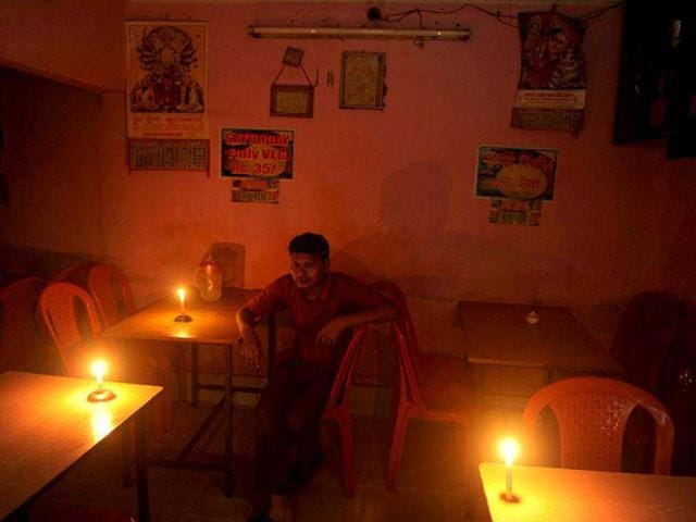 A diner waits for his meal in candle light at a hotel during a power cut in Siliguri. AFP/Diptendu Dutta