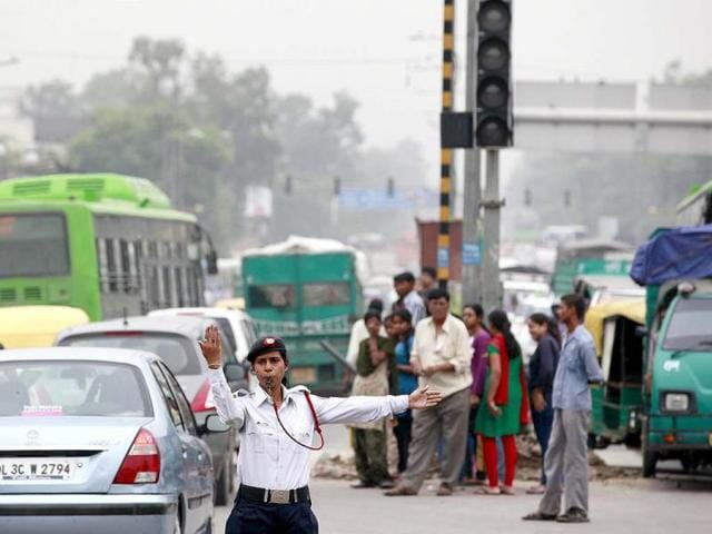 A traffic police officer directs traffic at an intersection during a power outage near Delhi University in New Delhi. HT/Raj K Raj