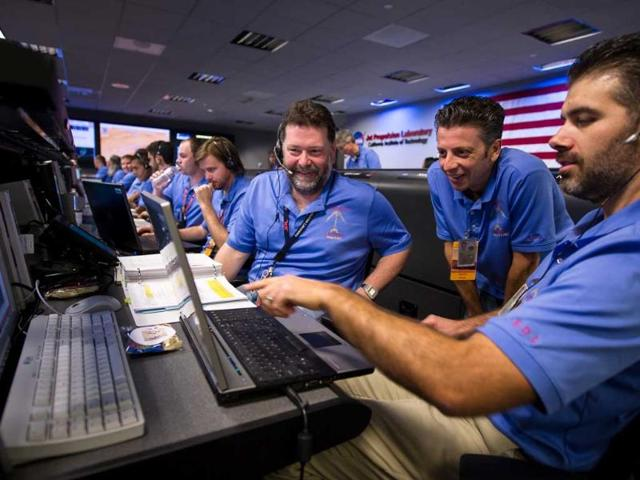 In-this-photo-released-by-NASA-s-JPL-Mars-Science-Laboratory-MSL-team-members-talk-in-the-MSL-Mission-Support-Area-at-the-Jet-Propulsion-Laboratory-ahead-of-the-planned-landing-of-the-Curiosity-rover-on-Mars-in-Pasadena-Calif-AP-NASA-Bill-Ingalls