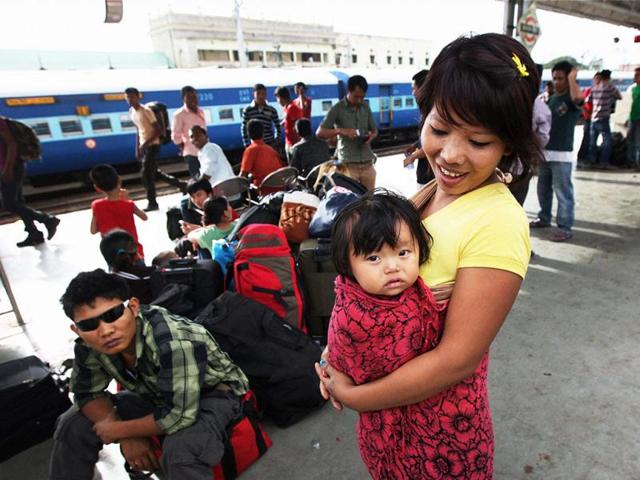 A-woman-holding-her-kid-as-people-from-northeast-wait-to-catch-a-train-at-Bengaluru-railway-station-to-return-to-their-homes-after-rumours-of-attacks-PTI-Photo-Shailendra-Bhojak