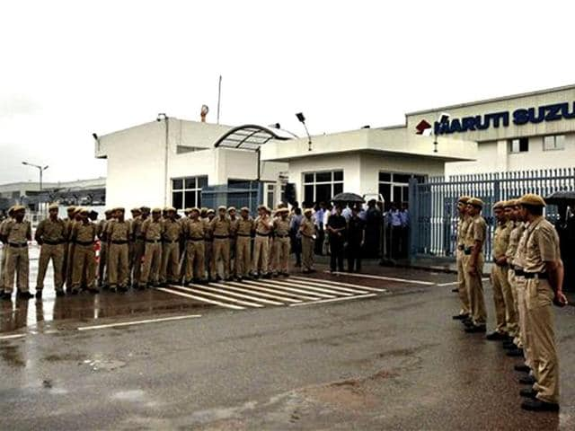 Security personnel stand outside the Maruti Suzuki factory at Manesar. The factory reopened with tightened security, after a riot by workers last month killed one person and injured dozens of others. AP Photo