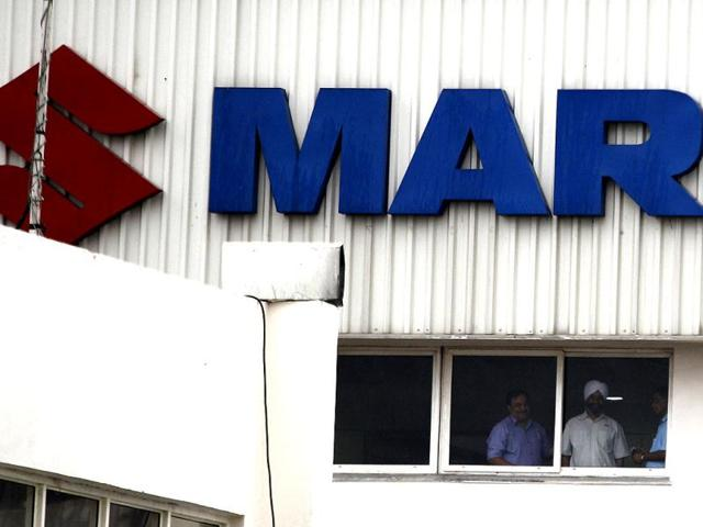 Employees of Maruti Suzuki look out from a window of their plant in Manesar. AP Photo