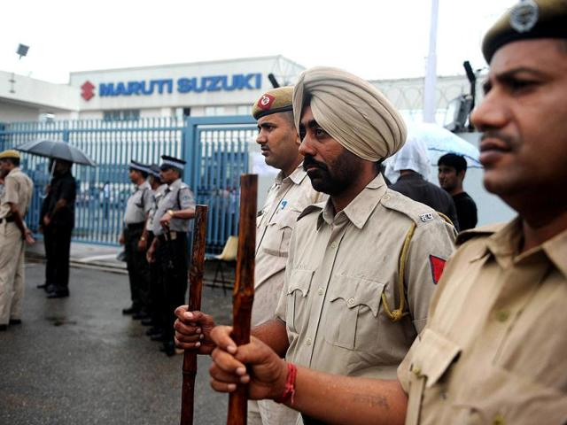 Policemen stand guard at the main gate of Maruti Suzuki Production Facllity in Manesar. AFP Photo