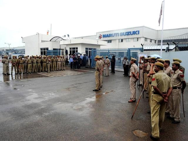 Policemen stand guard at the main gate of Maruti Suzuki Production Facllity in Manesar, about 56 kms from New Delhi. AFP Photo