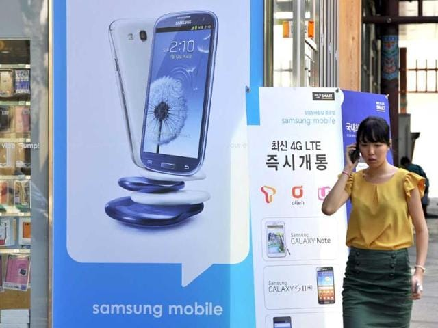 A-woman-walks-past-a-signboard-C-of-Samsung-Galaxy-S3-at-a-mobile-phone-shop-in-Seoul-AFP-Photo-Jung-Yeon-Je
