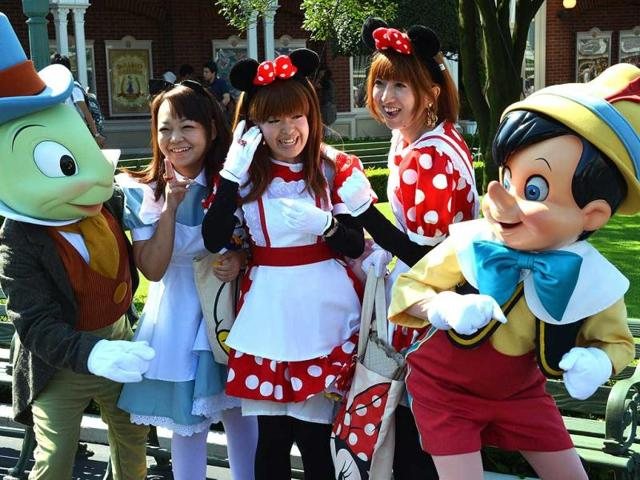 Visitors-dressed-in-teh-costumes-of-Alice-and-Minnie-Mouse-smile-with-Pinocchio-R-and-Jiminy-Cricket-L-mascots-at-the-Tokyo-Disneyland-in-Tokyo-AFP-Photo